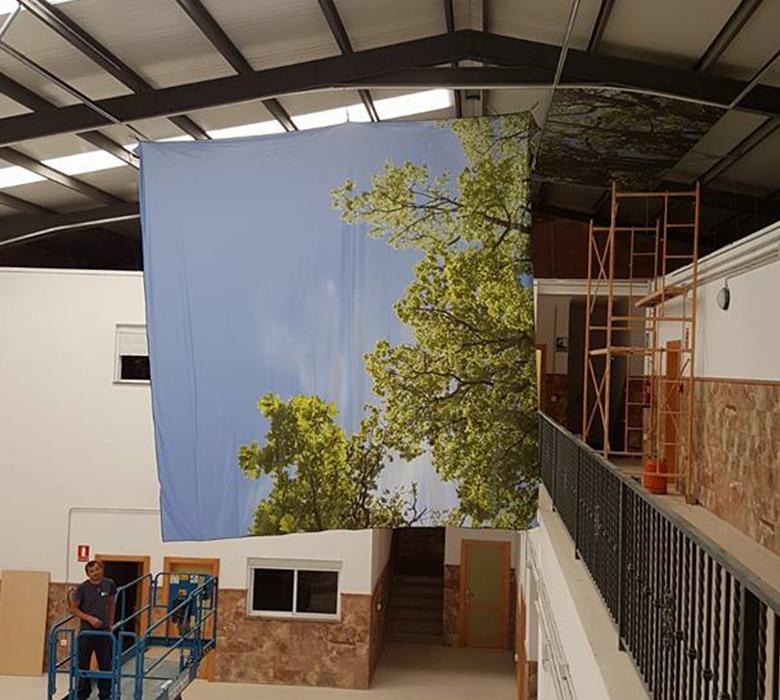 Colocación de la tela tensada impresa sobre el techo del Centro Oficial de Grado Superior de Córdoba