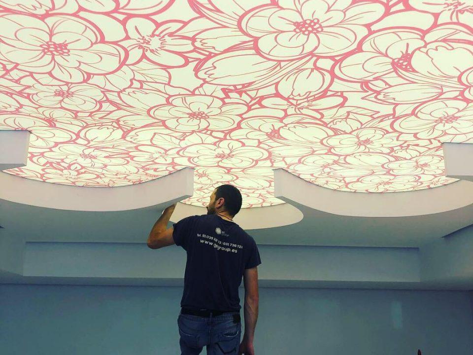 Trabajador de GS techos Tensados finalizando la instalación de la Tela tensada translúcida e impresa Barrisol